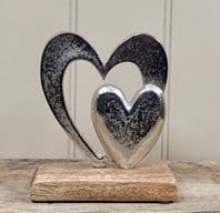 Double Heart Small Solid And Large Hollow. Silver Coloured Metal On Solid wood Base...